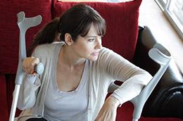 Femme assise sur un canapé avec des béquilles
