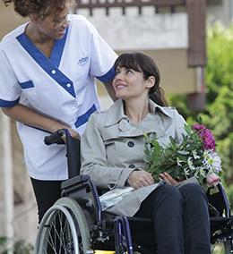 Personnel Adhap Services avec une femme en fauteuil roulant