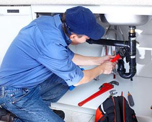 Plombier réparant une tuyauterie